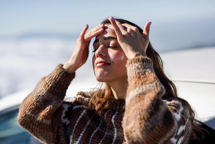 Mulher passando protetor solar.
